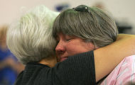 Pam Beard (cq), left, gives a hug to fellow evacuee Liz Armstrong (cq), right, at a meeting at the...