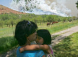 Amy Wright (cq), gives a kiss to her daughter Jade Wright (cq), 5, as smoke from a back fire fills...