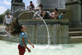 DLM0613  Water flies as Victoria Terrones, 9, flings her hair back while cooling off in the...