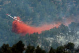 A slurry bomber drops fire retardant on the New Castle wildfire west of Glenwood Springs Tuesday...