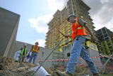 "Workers, subcontracted by ""Integrated Builders"", who would not identify themselves, walk..."