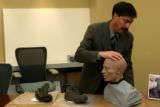 Mark Chavez, cq, Adams County Chief Deputy Coroner positions a forensic facial reconstruction bust...