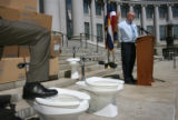 Mayor John Hickenlooper put his leg atop a toilet as Hamlet J. (Chips) Barry, III (cq), Manager of...