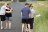 Damian Tate (cq) and Amanda Tate, (cq) of Brighton, Colo., hug while mourning the loss of Quinton...