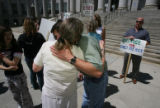 center foreground, Susan Garber, mother of the deceased, gets a hug from family friend Dan Duncan,...