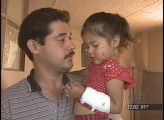 Jasmine Estrada, right, is held by her father at their home in the 3700 block of W. 3rd Ave. in...