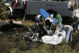 DLM0845  Recovery workers from Beegle's Aviation pick up the charred remains of a single engine...