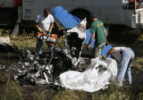 DLM0848  Recovery workers from Beegle's Aviation pick up the charred remains of a single engine...