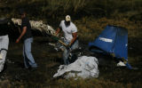 DLM0914  Recovery workers from Beegle's Aviation pick up the charred remains of a single engine...