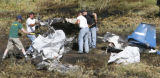 DLM0895  Recovery workers from Beegle's Aviation pick up the charred remains of a single engine...