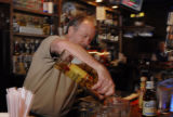 Reiver's Bar and Grille bar manager Doc Roberts (cq) pours a shot of tequila to a customer after...