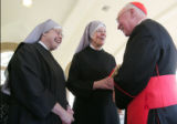 The Cardinal J. Francis Stafford visits with Sister paul, (left) and Mother Paul , center, both...
