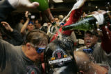 [234} Boston Red Sox pour the champagne during their celebration in the visitor clubhouse after...