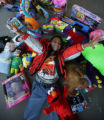 Ethan LaCrue, 6 is surrounded by toys that he hopes to give away on Saturday in Aurora, Colo. on...