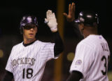 [6841]  Colorado Rockies first base coach Glenallen Hill congratulates Cory Sullivan after his...
