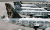 NYBZ122 - ** FILE ** A baggage tug passes by the tails of Frontier Airlines Airbuses sitting at...