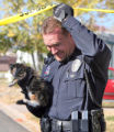 Federal Heights Police Officer Jon Hess (cq) removes a cat from the home of the shootings at the...
