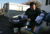 Michael Ruiz (cq) wipes down his car as investigator are inside the trailer next door where a...