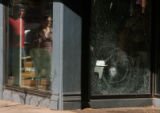 Pedestrians walk by the Patagonia store at the corner of 15th and Blake in which a bullet tore...