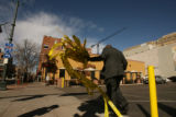 A member of the Denver Police Department retrieves the crime tape from the corner of 15th and...