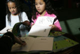 Trinity Jones (cq), 7, left, and her sister Kellsie Forfar-Jones (cq), 10, ask authors Abi Waldman...