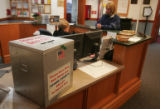 Merrie Cox (cq) drops off her ballot at the Brighton City Clerk's office Tuesday night November6,...