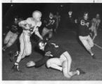 Action photo of Fred Tesone. Four distinguished individuals and the 1954 football team were...