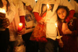 DM0417   Diamond Duran, 6, clings to family members during a candlelight vigil at the location...