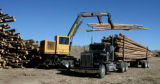 Jeff Pitts (cq) unloads a trailer of logs in the yard of Confluence Energy's new facility, Highway...