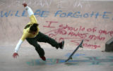 Zach Baca (cq), 19, falls off his board doing a trick next to grafitti for Ethan Tetter at the...