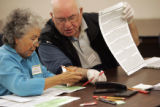Lucille Ellis and Emilio Sanelli work on incorrectly filled out ballots so they can be reconciled...