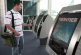 Joe Crosbie (cq) of Eagle, Colo. gets his ticket at Frontier's bank of  new check-in kiosks at DIA...
