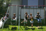 Five members of the Mesgana Dancers sit with their dolls on a swing in Littleton, Colo., before...