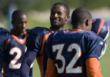 The Denver Broncos cornerback Champ Baily, left, smiles at fans as he joins fellow cornerback Dre...