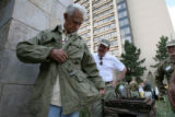 Nelson Bennett, cq, (left) of Yakima, WA, shows of his coat he wore in a foxhole in Italy in 1945...