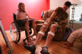 DLM5198  Emily Blood, 10, watches as her uncle, Andy Blood, 27, straps braces to his legs that...