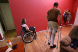 DLM5208  Emily Blood, 10, left, watches from her uncle's wheelchair as he walks with the help of...