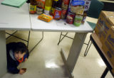 (DENVER, Colorado October 01, 2004)Cristian Cerillo Heredia, 2, plays under a table of food at...