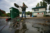 Fredo Arredondo (cq) dumps depris as he clears his property from a flood at the Park Lane  Mobile...
