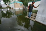 Fredo Arredondo (cq) stands by his shed still marked with a water line as he clears his property...