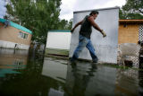 Fredo Arredondo (cq) walks by his shed still marked with a water line as he clears his property at...