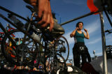 Nancy Stevens (cq) (at right), adjusts her helmet at the transition area where she will ride a...