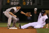 Rockies Todd Heltonslides into second base before the tag by Pirates shortstop Jack Wilson in the...