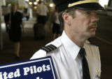 Ken Woosley(cq), a pilot for United Airlines for 20 years, marches outside of the United ticket...
