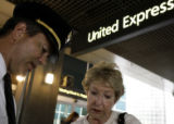 Ron Creighton, an United Airlines pilot for 12 years, hands a pamphlet to Martie Crawford(cq),...