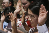 28 year-old Maria Diaz de Jesus (cq) (at right) takes the oath to become a United States Citizen,...