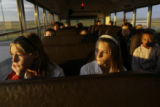 Rachel Mathis(cq)(left) , 13, and her twin sister, Crystal(cq), ride the bus to their first day of...