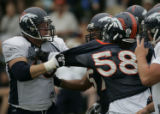 Bronco LB,  T.J Hollowell, center, tries to separate OT Adam Meadows, left, #77 and  Nate Webster...