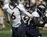 QB Jay Cutler hands off the ball to #20 Travis Henry runs the ball during practice at the Denver...
