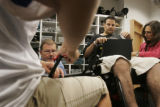 (JOE0640) - Tommy Urbanski, in black shirt, holds a pad as he has his electric wheelchair adjusted...